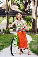 Portrait of a mature woman standing with a bicycle