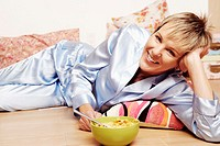 Portrait of a mature woman lying on the floor with a bowl of corn flakes