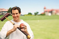 Portrait of a mid adult man holding a croquet mallet and a ball