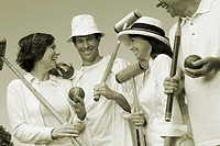 Low angle view of a mid adult couple and a mature couple holding croquet mallets and balls