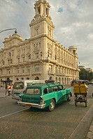 Turquoise 1955 Buick car and bicycle taxi driving the streets of Old Havana