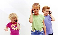 Three young children play with cell phones
