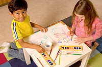 Portrait of Hispanic boy and Caucasian girl painting