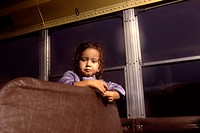 A small girl poses inside a school bus