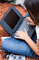 Over the shoulder view of a young girl using her laptop while sitting on a rug
