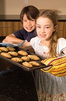 Portrait of Asian boy and Caucasian girl with cookies