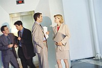 Business associates talking by elevator