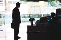 Businessman standing speaking to receptionist, silhouette
