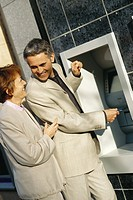 Mature couple standing at ATM machine