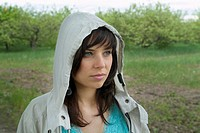 portrait of young woman in garden wearing jacket with hood