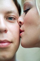 close-up of young woman kissing man on cheek