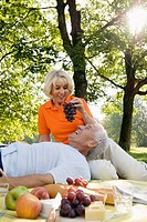 mature woman feeding man grapes at picnic in park