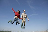 couple holding hands and jumping for joy