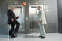 Businessmen Playing Soccer by Elevator