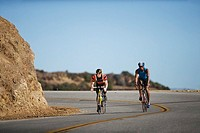 Cyclists Rounding a Curb During a Triathlon