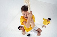 Schoolboy Climbing Rope in Gym Class