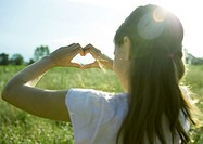 Girl in field, making heart shape with hands, rear view