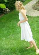 Young woman standing in yard, wearing sundress, smiling at camera