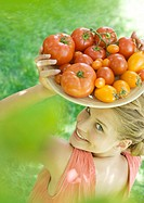 Young woman holding up bowl of tomatoes, smiling at camera