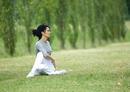 Young woman stretching on grass
