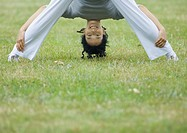 Young woman doing standing forward bend, looking through legs at camera, smiling (thumbnail)