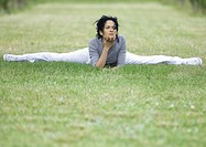 Young woman doing splits in grass