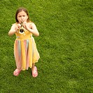 Girl Playing Toy Trumpet in Garden