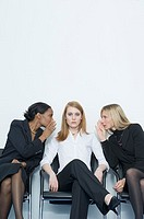 Portrait of a businesswoman sitting on a chair with two businesswomen on either side whispering into her ears