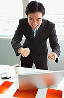 Businessman standing, looking at laptop, making a face