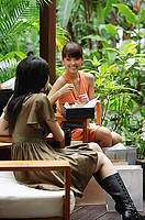 Two young women in outdoor cafe, shopping bags around them