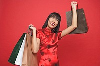 Woman in red cheongsam, carrying shopping bags, looking up