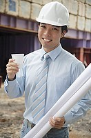 Businessman wearing hardhat, carrying blueprints and a cup