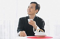 Man drinking tea, looking away