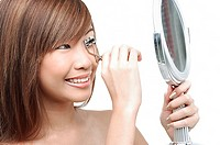 Teenage girl using eyelash curler, looking in mirror
