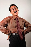 Nerdy businessman with hands on hips, laughing