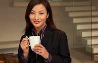 Businesswoman looking at camera, holding mug