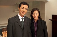 Business people standing side by side, smiling at camera