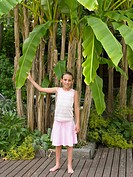 Girl holding the leaf of a large plant