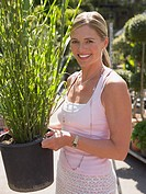 Woman holding a plant in garden centre