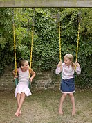 Two girls playing on swings