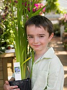 Boy holding plant in a garden centre