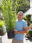 Man holding a plant in garden centre