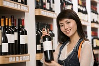 Woman displaying bottle of wine in wine shop