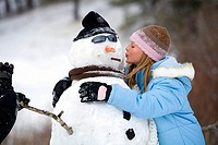 Girl kissing a snowman