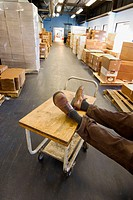 Man´s feet, wearing shoes, resting on a rolling cart in a factory´s storage area.