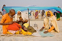 sadhus after their bath in the sacred Ganges, taking care of their belongings, during the Ardh Kumbh Mela 2007 in Prayag