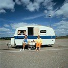 Portrait of a mature couple sitting on the outside of their recreational vehicle