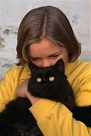A Caucasian girl looking down and holding a black cat