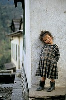A sweet girl standing near the wall