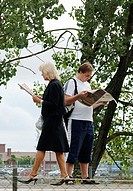 Mature man and mature woman reading newspapers